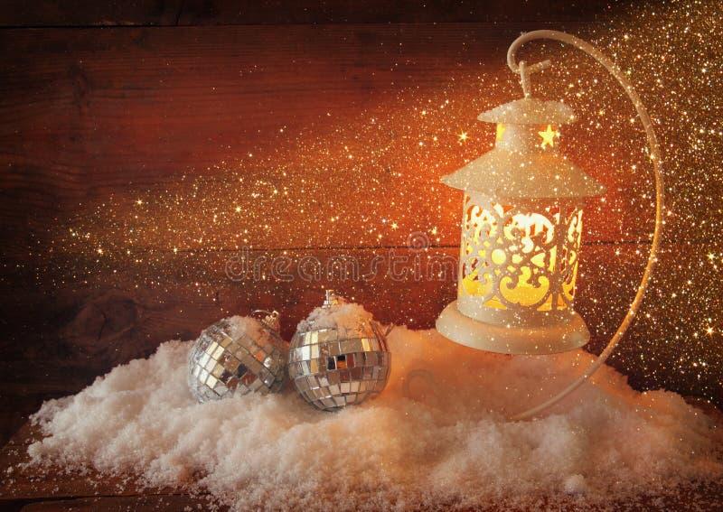 Fond de Noël avec la lanterne, la babiole et la neige blanches au-dessus du fond en bois photos libres de droits