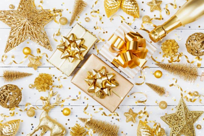 Fond de Noël avec le cadeau d'or ou la boîte, le champagne et les décorations actuels de vacances sur la vue supérieure blanche d photos stock
