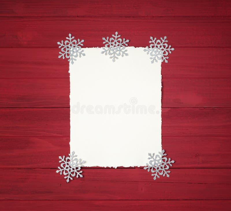 Fond de Noël avec le papier de cru avec les bords en lambeaux et les décorations de flocon de neige sur rustique, panneaux en boi photos stock