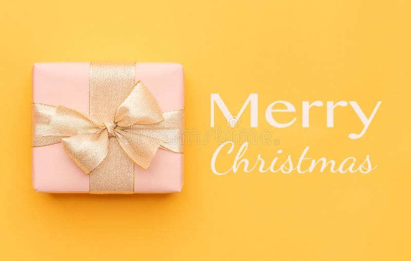 Fond de Noël Beau cadeau de Noël d'isolement sur le fond jaune lumineux Boîte rose de Noël photos libres de droits