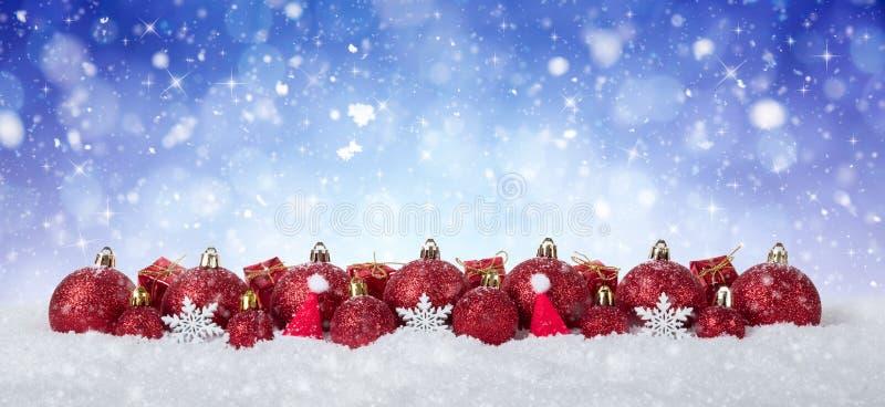 Fond de Noël - boules rouges décorées sur la neige avec des flocons de neige et des étoiles photos libres de droits