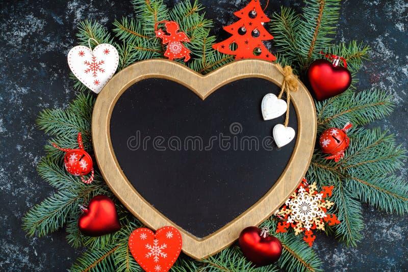 fond de Noël - décorations et branche de sapin sur une table, un cadre sous forme de coeur, vue supérieure, endroit pour le texte image libre de droits