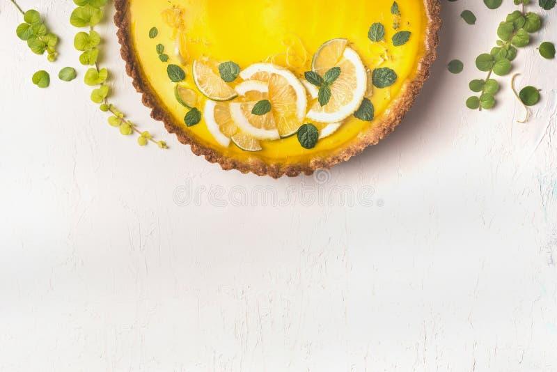 Fond de nourriture avec la tarte de citron complétée avec des tranches et l'entrain d'agrume sur le fond blanc de table, vue supé photos stock