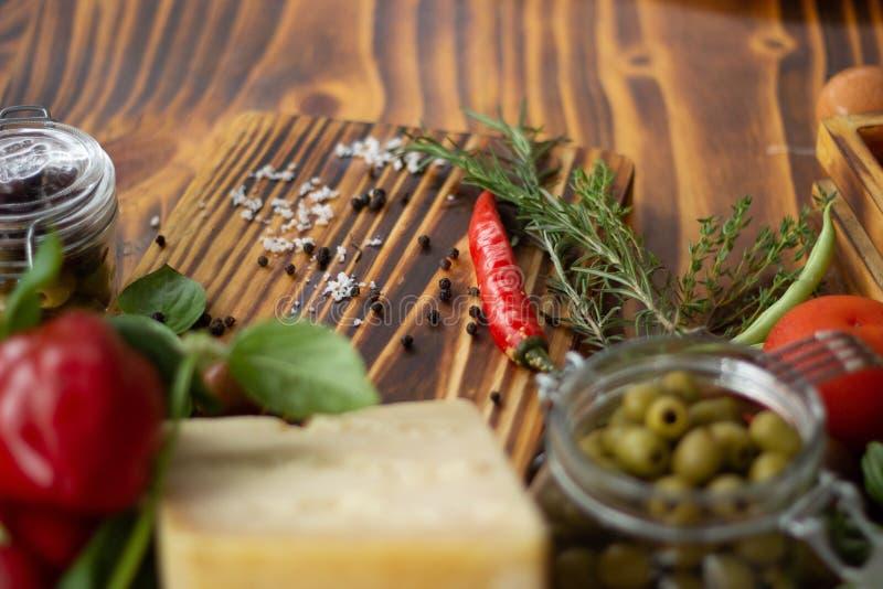 Fond de nourriture sur la table en bois Fromage de plan rapproché, poivrons, olives vertes, tomates et épices pour faire cuire la photo stock