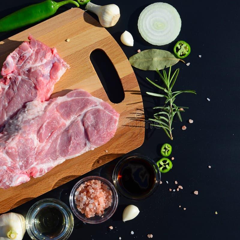 Fond de nourriture Viande sur une planche à découper et poivre, feuille de laurier, romarin, oignons, sel de l'Himalaya, huile d' photos libres de droits