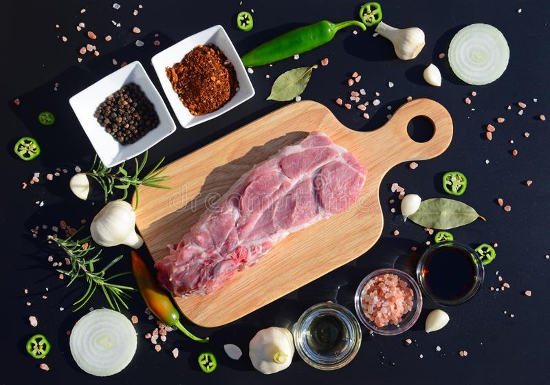 Fond de nourriture Viande sur une planche à découper et poivre, feuille de laurier, romarin, oignons, sel de l'Himalaya, huile d' image libre de droits