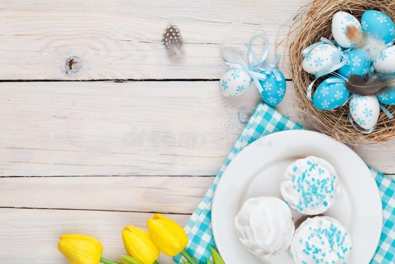 Fond de Pâques avec les oeufs bleus et blancs dans le nid, tulipe jaune image stock