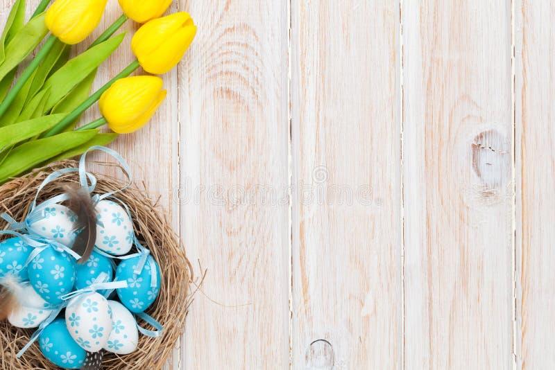Fond de Pâques avec les oeufs bleus et blancs le nid et au TU jaune images stock