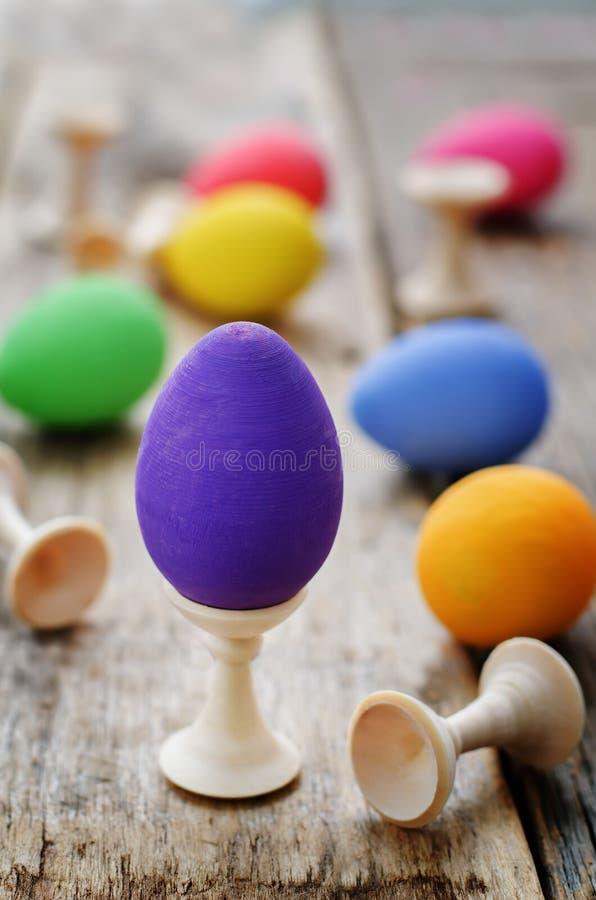 Fond de Pâques avec les oeufs colorés sur des supports photos stock
