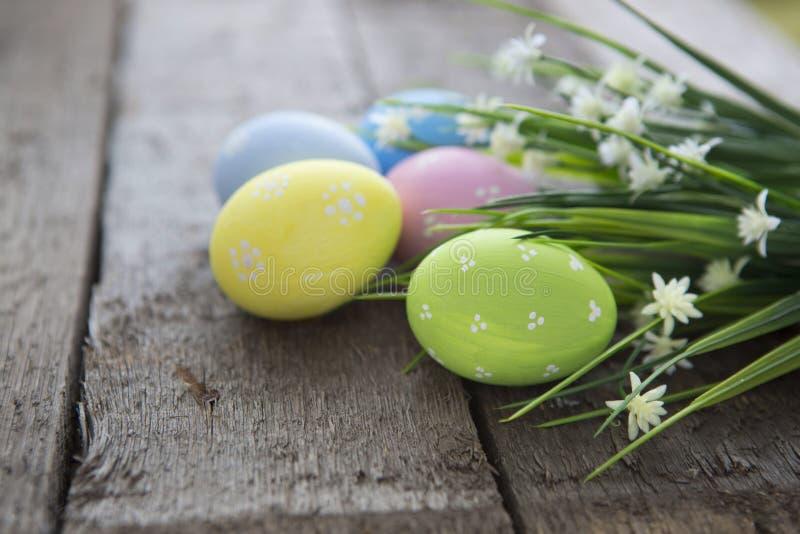 Fond de Pâques avec les oeufs et les fleurs colorés au-dessus du bois photo stock