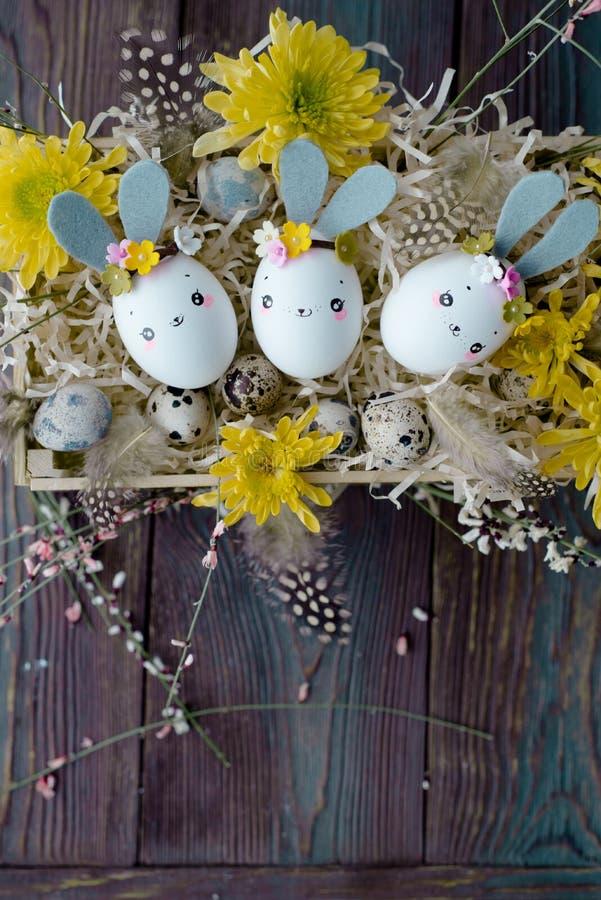 Fond de Pâques, lapins faits maison de coquille d'oeuf et chrysanthème jaune dans la boîte en bois photo stock
