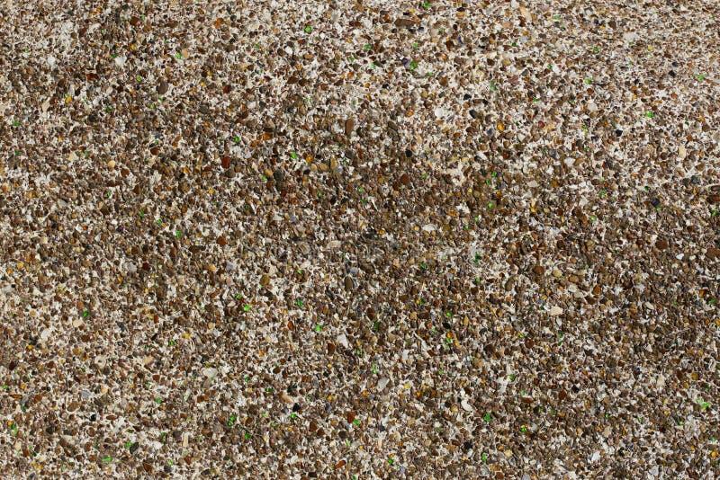 Fond de petits cailloux, de fragments en verre colorés et de morceaux de coquilles de mer photographie stock libre de droits