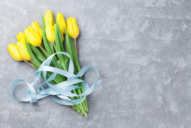 Fond de pierre de carte de Pâques avec les tulipes jaunes photos stock