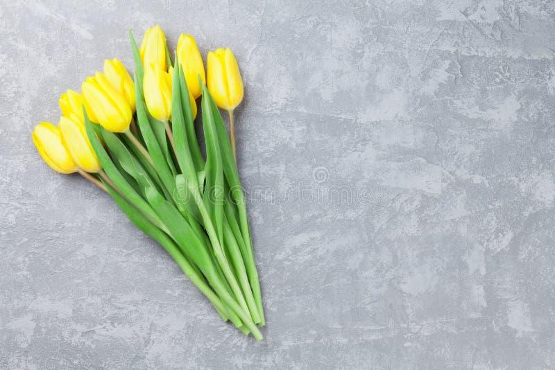 Fond de pierre de carte de Pâques avec les tulipes jaunes images stock