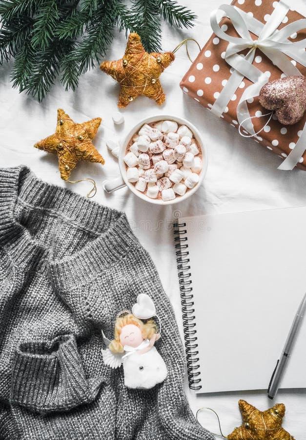 Fond de planification de Noël - chocolat surdimensionné et chaud de chandail tricoté confortable gris, cadeaux de Noël et décorat photos stock