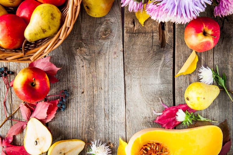 Fond de récolte ou de thanksgiving avec le cadre des fruits, des fleurs, de la courge et des feuilles automnaux sur une table en  images libres de droits