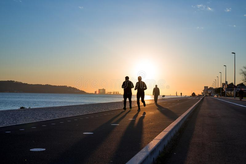 Fond de séance d'entraînement, deux personnes pulsant sur le bord de mer au coucher du soleil, silhouettes de coureurs, concept s photo libre de droits