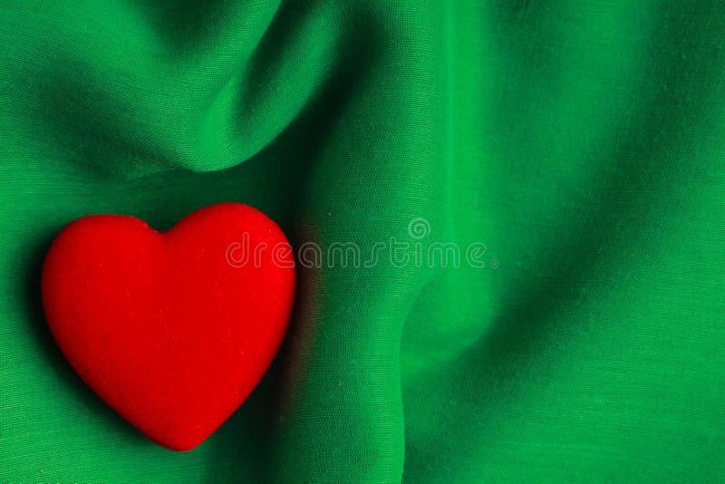 Fond de Saint-Valentin. Le coeur rouge sur le vert plie le tissu photographie stock