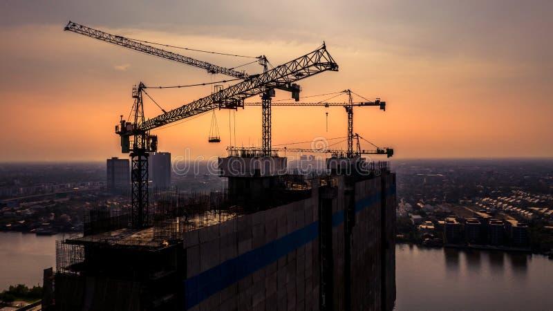 Fond de silhouette de chantier de construction, levant des grues et de nouveaux bâtiments à plusiers étages, fond industriel de v image libre de droits