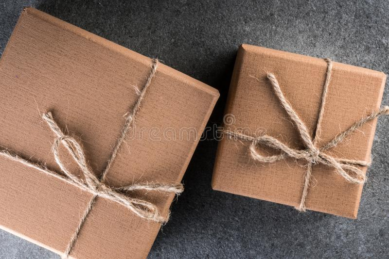 Fond de vacances avec les boîte-cadeau bruns avec le ruban sur le fond foncé de vintage Moquerie vers le haut des boîte-cadeau et photos stock