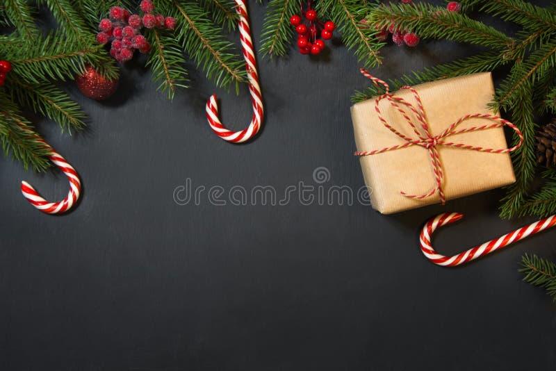 Fond de vacances de Noël - arbre, cadeaux, baies de houx et décoration sur le chackboard noir Carte de vacances avec l'espace de  images stock