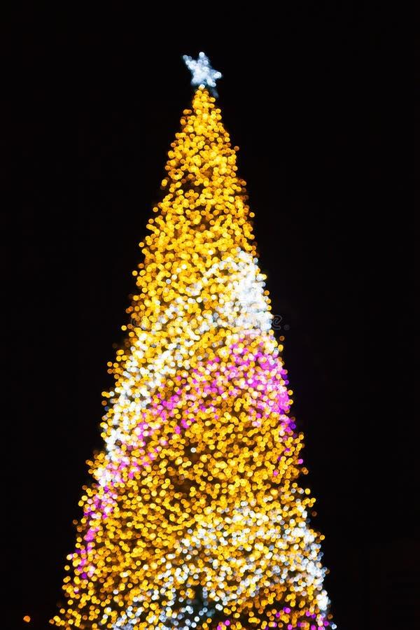 Fond defocused de scintillement rougeoyant éclatant d'illumination de bokeh de lumière de nuit d'or avec l'arbre de Noël décoré s image libre de droits