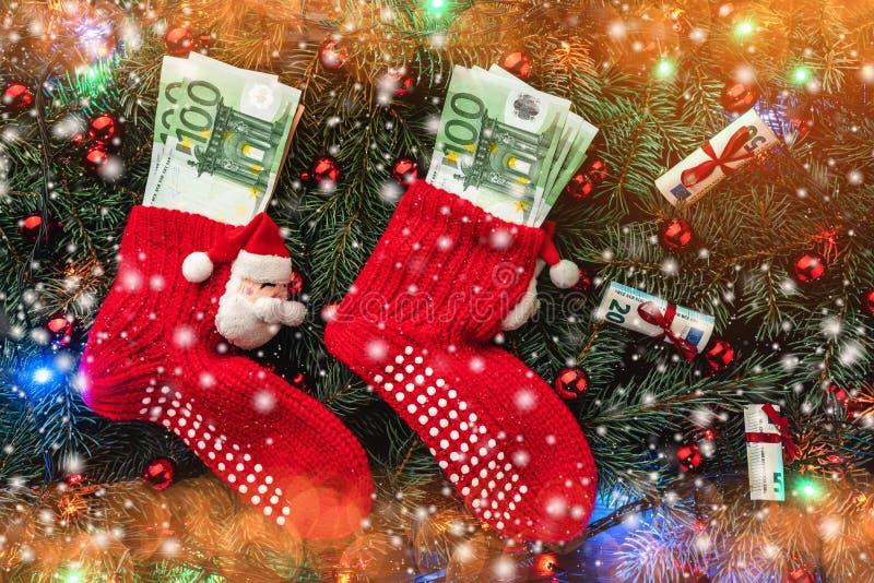 Fond des branches de sapin Les bas rouges de Santa avec l'argent Carte de Noël Vue supérieure Félicitations de Noël lumières photos stock