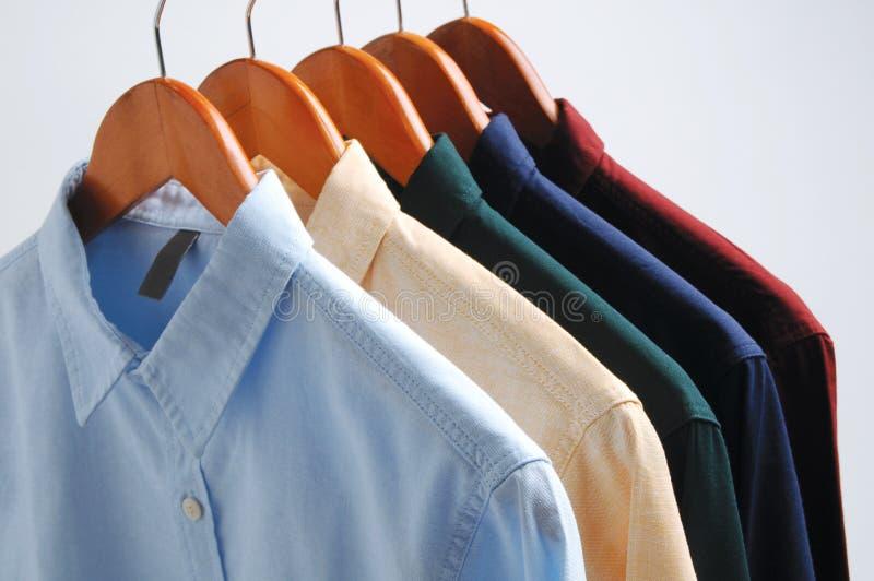 Fond des chemises accrochant sur un cintre images stock