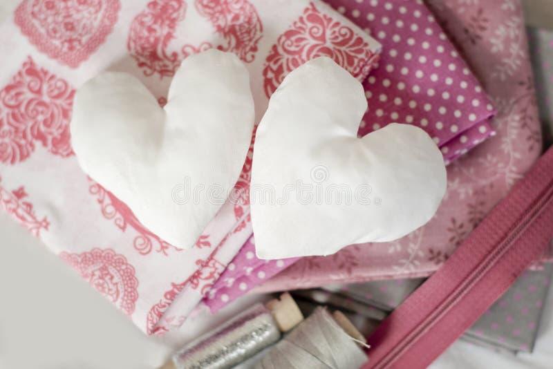 Fond des coeurs blancs de textile et les outils et les accessoires de couture dans rose - image photo libre de droits