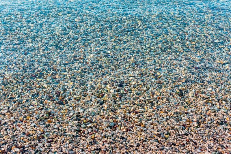 Fond des pierres colorées lumineuses brouillées de mer sous l'eau Lumière du soleil iridescente sur les pierres L'eau claire de l images libres de droits