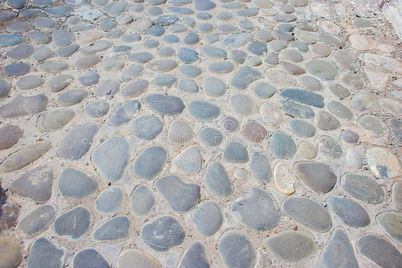 Fond des pierres grises lisses qui sont présentées sur la route Texture photo libre de droits