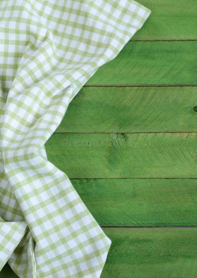 Fond en bois avec la serviette de cuisine verte photos stock