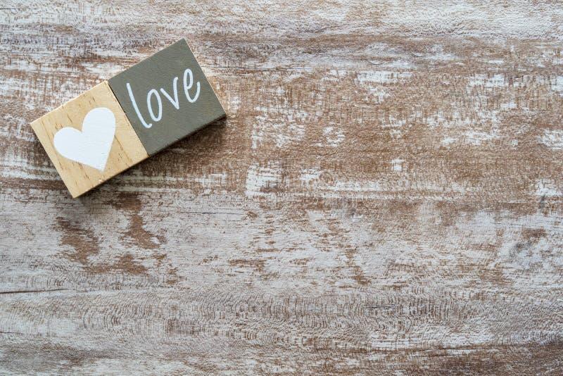 Fond en bois confortable dans les tons blancs et grisâtres, avec un coeur en bois blanc et l'amour de mot sur un autre morceau de photo libre de droits