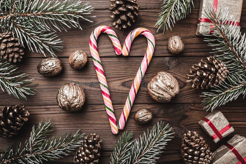 Fond en bois de Brown Branches de sapin, cônes et noix décoratives Sucreries colorées Cadeaux pour Noël photographie stock