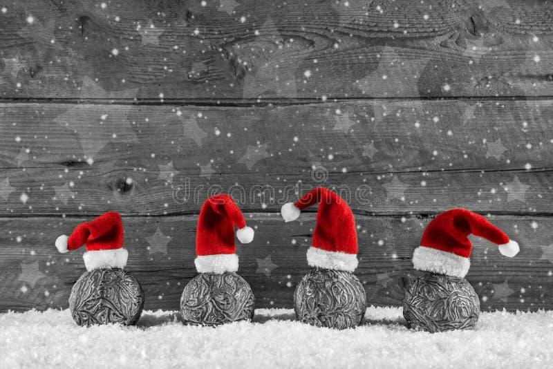 Fond en bois de fête gris de Noël avec quatre chapeaux de Santa dessus photographie stock libre de droits
