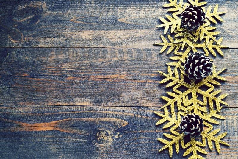 Fond en bois de Noël avec les flocons de neige et les cônes décoratifs de pin photographie stock libre de droits