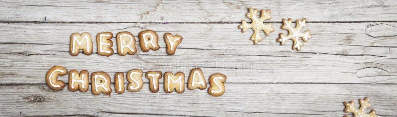 Fond en bois gris de Christmassy avec le pain d'épice et la joyeuse lettre du ` s de Christma image libre de droits