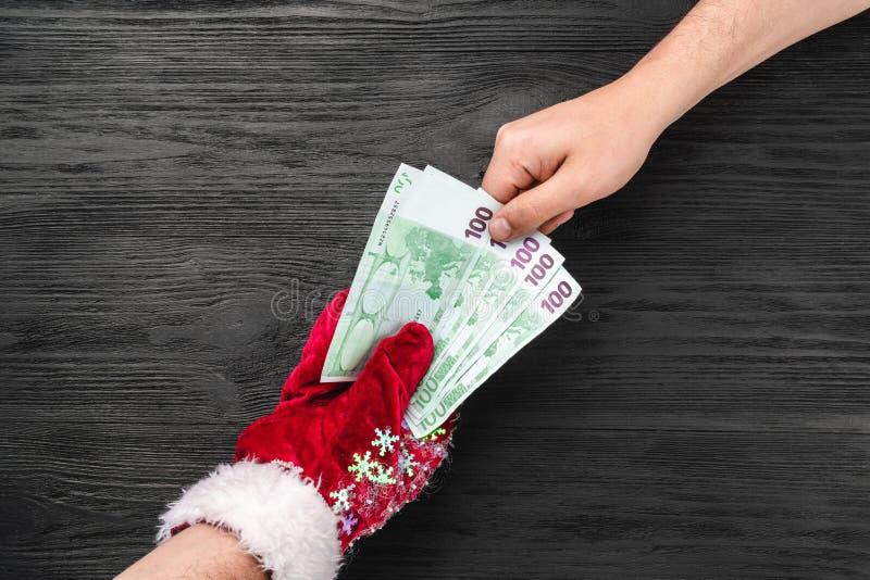 Fond en bois noir Le cadeau de Santa pour vous Carte de Noël Vue supérieure Félicitations de Noël Claus donne l'argent photo stock