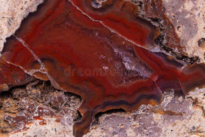 Fond en cristal de texture Plan rapproché de cristal minéral rouge-brun qui a enfermé dans en pierre et poli Macro images stock