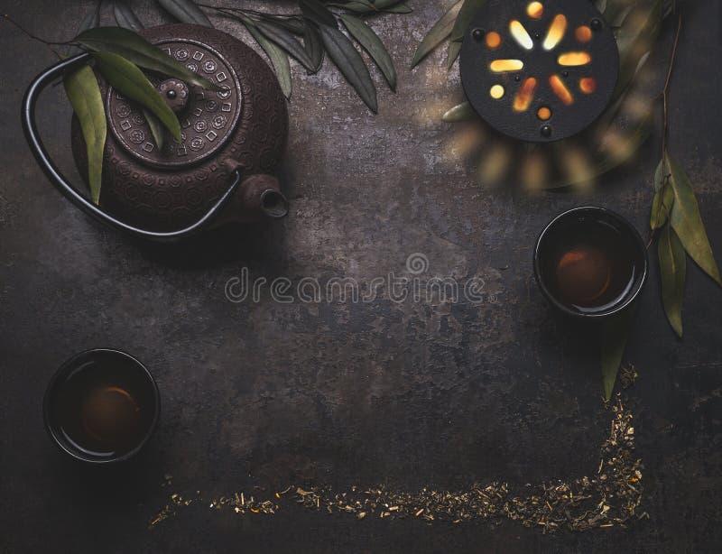 Fond foncé de thé avec la théière de fer noir et la tasse asiatiques de thé chaud sur la table rustique, vue supérieure, cadre co image libre de droits