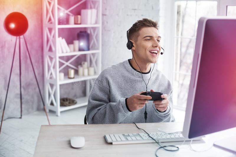 Modern handsome student fond of video games feeling joyful while playing stock images