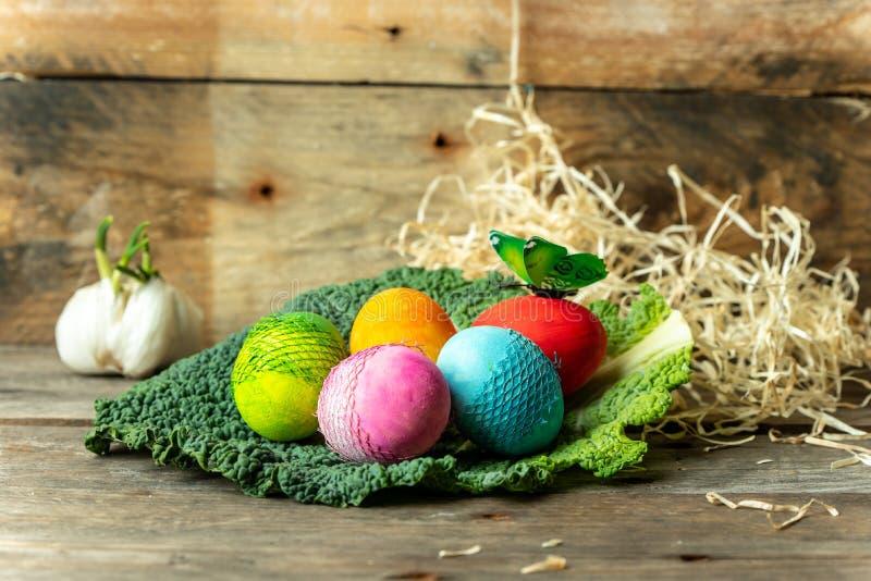 Fond heureux de carte de Pâques - en pastel, oeufs de pâques peints à la main, doux, colorés sur une table en bois simple et rust photo libre de droits