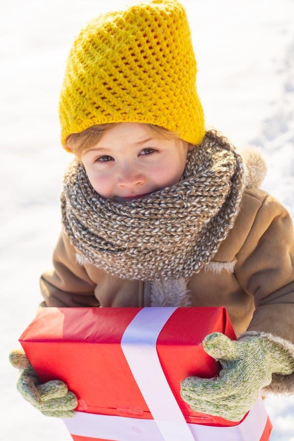 Fond heureux de neige d'arc de cadeau de prise d'enfant d'hiver Petits vêtements chapeau d'hiver d'usage de garçon et fin d'échar images libres de droits
