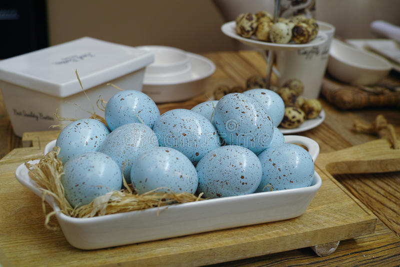 Fond heureux de Pâques avec les oeufs de pâques bleus sur le tabl en bois image stock