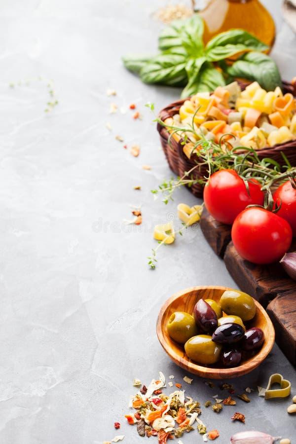 Fond italien de nourriture avec des tomates de vigne, basilic, spaghetti, ingrédients d'olives sur l'espace en pierre de copie de image stock