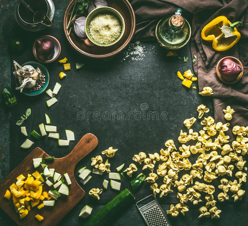 Fond italien de nourriture Pâtes végétariennes crues de tortellini avec des légumes et des herbes sur le fond rustique foncé de t images libres de droits