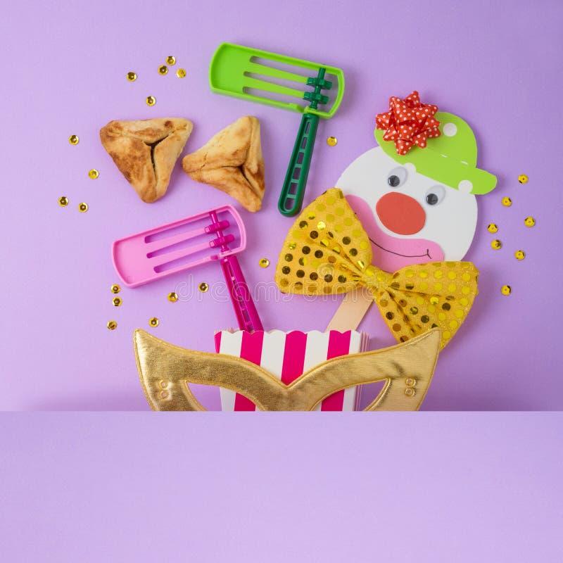 Fond juif de Purim de vacances avec le masque de carnaval, le clown de papier et hamantaschen des biscuits images stock