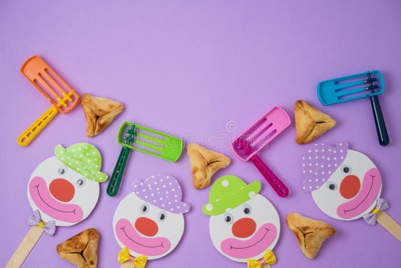 Fond juif de Purim de vacances avec le masque de carnaval, le clown de papier et hamantaschen des biscuits photo stock