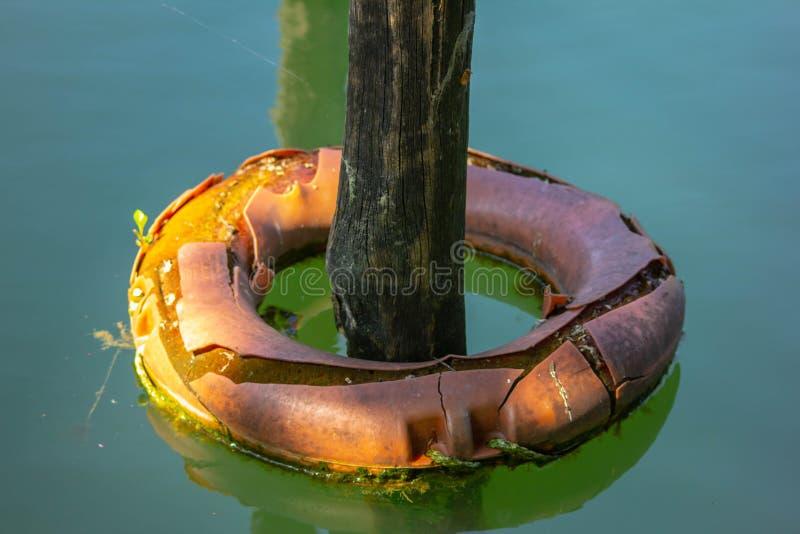 Fond le poteau émergeant de l'eau avec un conservateur de vie l'entourant s'accouplait avec des bateaux sur la rivière de Sile images stock