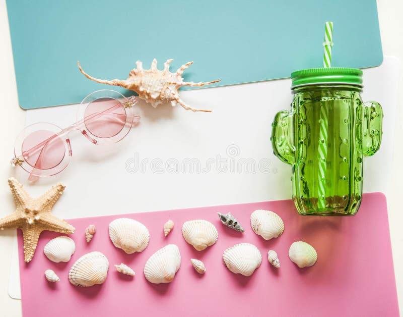 Fond lumineux d'été avec le voyage Coquillages, lunettes de soleil, un verre pour des cocktails sur un fond blanc bleu de rose photo stock